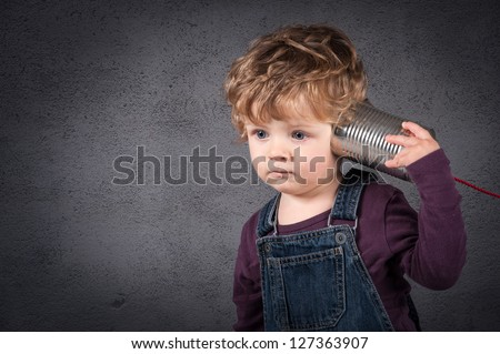 Young kid listen to tin can telephone over grunge background. - stock photo