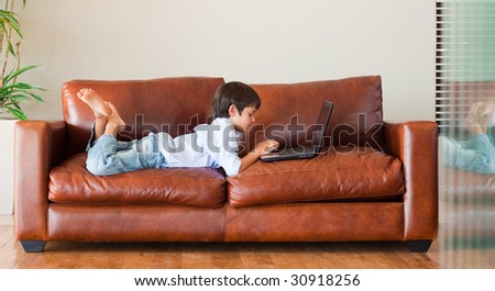 Young kid playing with a laptop on the sofa - stock photo
