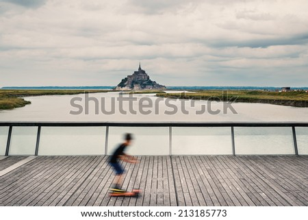 Young kid running with scooter on the dam with Mont Saint Michel abbey in the background. Normandy, France.  - stock photo
