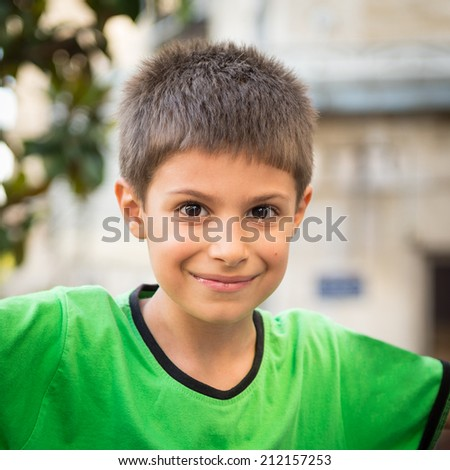 Young kid smiling outdoors portrait.  - stock photo