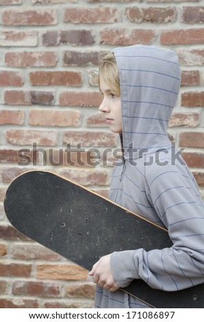 young kid walking down the street with his skate board - stock photo