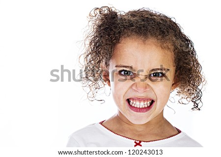 Young kid with a hostile expression of anger on her face. - stock photo
