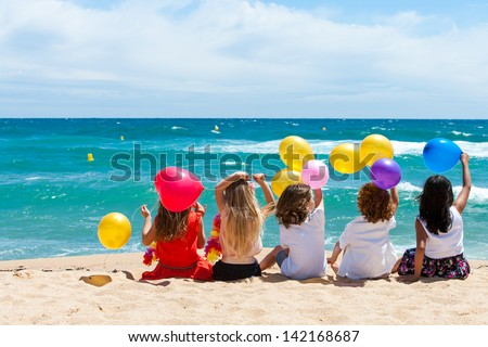 Young kids holding color balloons sitting on beach. - stock photo