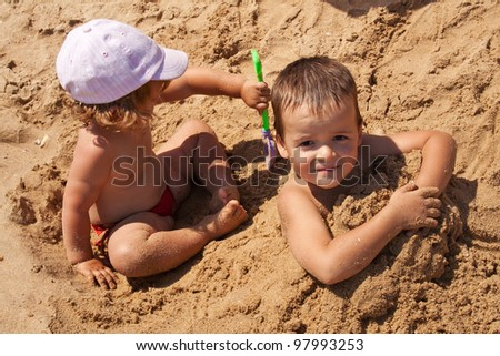Young kids playing in golden sand - closeup - stock photo