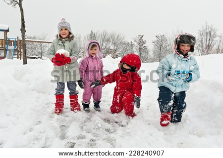 Young kids playing in the snow.  - stock photo