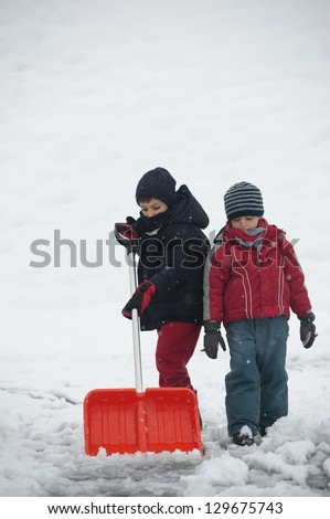 Young kids shoveling snow off sidewalk. - stock photo