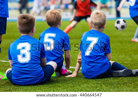 Young Kids Soccer Team. Reserve Players Sitting Together and Watching Football Soccer Tournament Match for Youth Teams. - stock photo