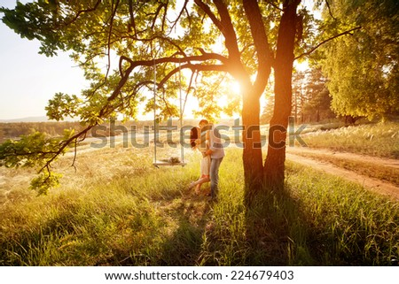 Young kissing couple under big tree with swing at sunset - stock photo