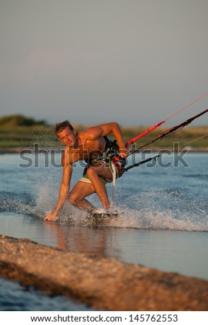 young kiter-athlete ride against the setting sun and the spray of the sea - stock photo