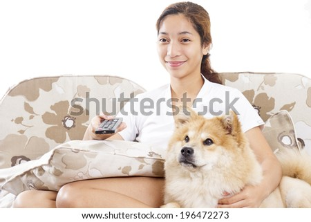 Young lady and a dog watching and enjoying a television program. - stock photo