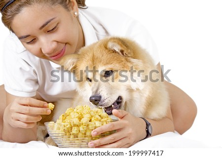 Young lady and a pet dog enjoying a bowl of popcorn. - stock photo