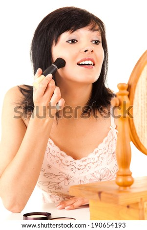 young lady applying make up, white background - stock photo