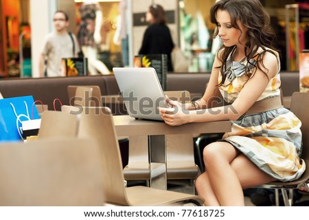 Young lady browsing the Internet at the cafe - stock photo