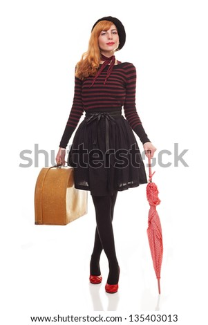young lady carrying a retro suitcase and an umbrella posing.isolated on white background - stock photo