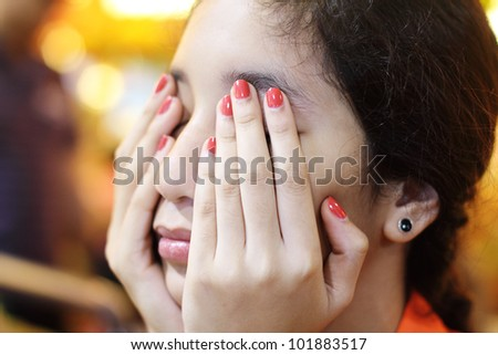Young lady covering her eyes and face with hands while resting. - stock photo