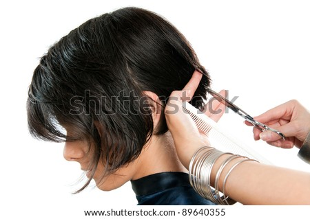 Young lady cutting hair at the hairdresser isolated on white background - stock photo