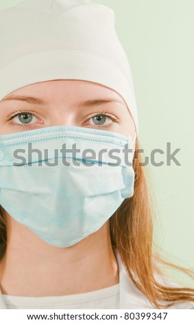 Young lady doctor wearing the mask - stock photo