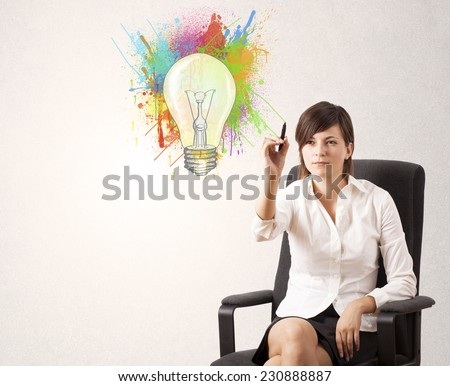 Young lady drawing a colorful light bulb with colorful splashes on white background - stock photo