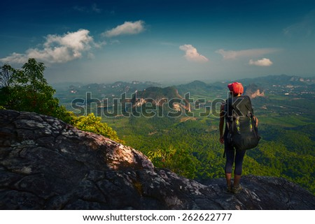 Young lady hiker with backpack standing on top of the mountain and enjoying valley view - stock photo