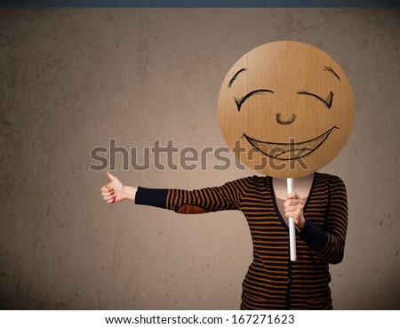 Young lady holding a cardboard smile face emoticon in front of her head - stock photo