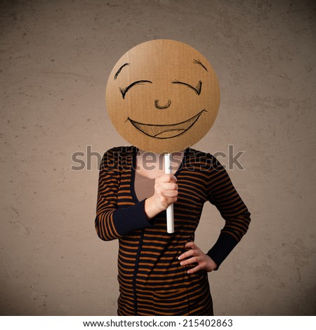 Young lady holding a cardboard smiley face emoticon in front of her head - stock photo