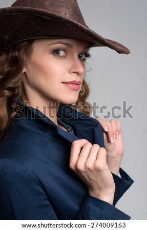 Young lady in a cowboy hat. Studio portrait - stock photo