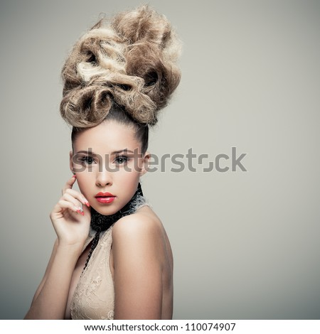 Young lady in fashionable dress posing on grey background - stock photo