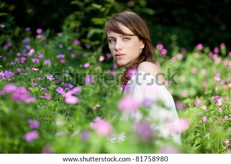 Young lady is surrounded by summer flowers - stock photo