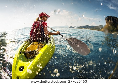 Young lady paddling the kayak in the sea with lots of splashes - stock photo