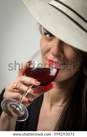 Young lady portrait tasting red wine in a attractive, sexy style. - stock photo
