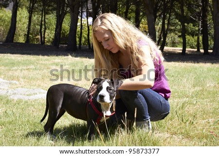 Young lady putting leash on Pit Bull dog breed - stock photo