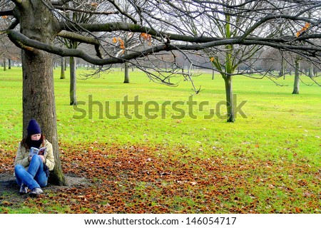 Young lady reading in Hyde Park, London, UK  - stock photo
