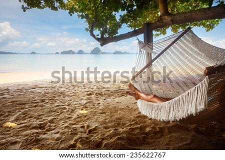 Young lady relaxing in hammock on the sandy beach - stock photo