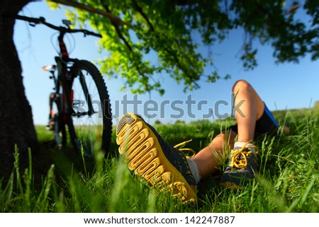 Young lady relaxing on a green meadow after cycling. Focus on a foot - stock photo