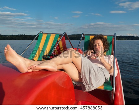 Young Lady Relaxing with Legs Up in a Public Paddle Boat by the Lake - stock photo