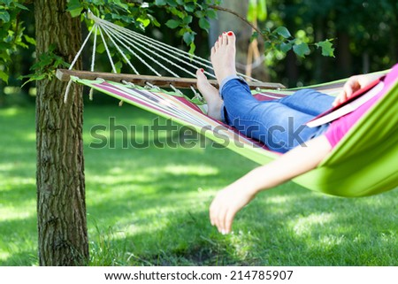 Young lady resting on hammock with book summer - stock photo