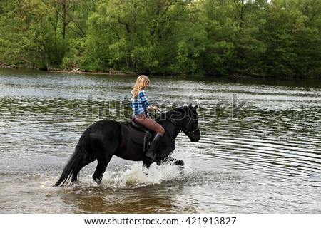 Young lady riding horseback in the river - stock photo