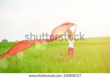 Young lady runing with tissue in green field. Beautiful happy woman walking  in the summer rural meadow. Pretty sport style woman jumping with fabric. Beautiful fit tan girl. Caucasian outdoors. - stock photo