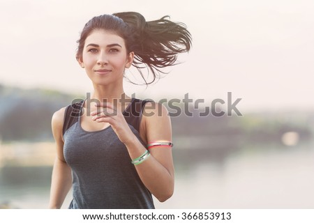 Young lady running on a beach during morning with wearable devices - stock photo