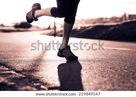 Young lady running on a road during sunset. Selective focus. Low depth of field. Detail of sport feet on trail. Black and white photography. Sepia. Cream tone. - stock photo