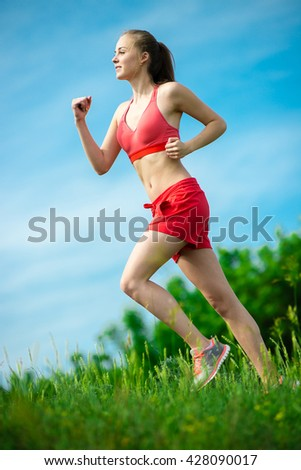 Young lady running. Woman runner running through the summer park rural road. Workout in a park. Beautiful fit girl. Fitness model caucasian ethnicity outdoors. Weight loss exercise. Jogging. - stock photo