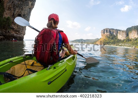 Young lady sits in the kayak with a paddle in the sea - stock photo
