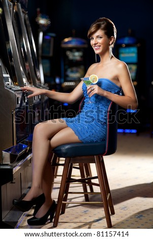 young lady sitting by the slot machine, posing with cocktail - stock photo