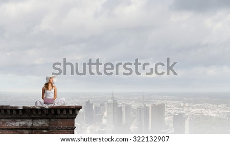 Young lady sitting on building roof and using laptop - stock photo