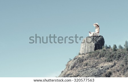 Young lady sitting on top of mountain with laptop - stock photo
