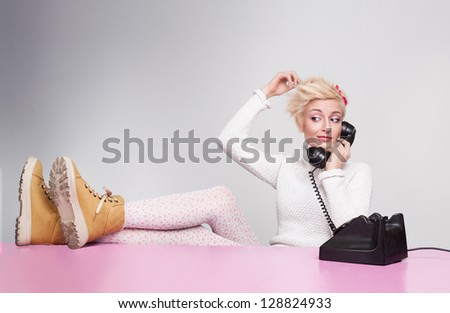 young lady speaking on the phone while her legs on the desk - stock photo