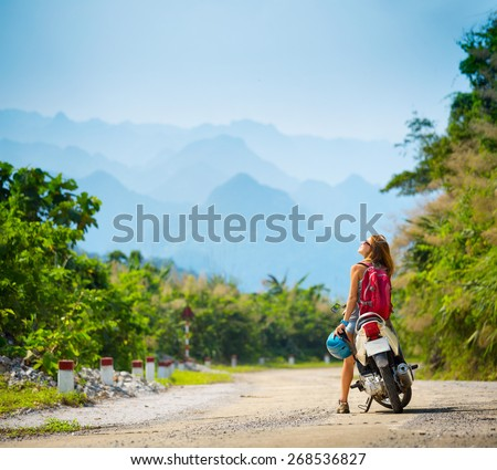 Young lady standing near motorbike and enjoying landscape view - stock photo