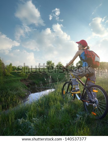 Young lady standing with bicycle on a wild meadow by a river at sunset - stock photo