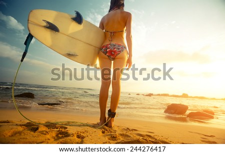 Young lady standing with surf board on the tropical beach - stock photo