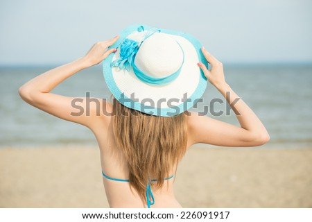 Young lady sunbathing on a beach. Beautiful woman posing at the summer sand beach. Outdoor summer portrait of pretty sport style woman in blue bikini.  - stock photo